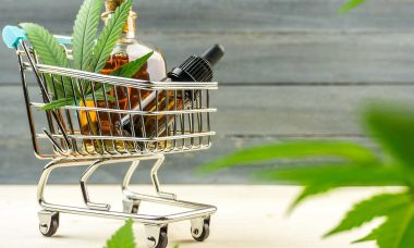 Supermarket trolley with marijuana leafs and medical cannabis oi